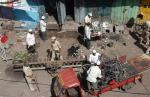 Local residents and police officers clear debris at a blast site in Malegaon