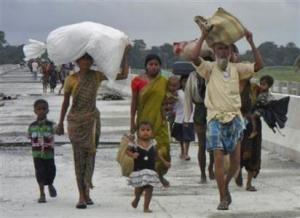 Villagers with their belongings move to relief camps as they leave their locality after violence at Chirang district